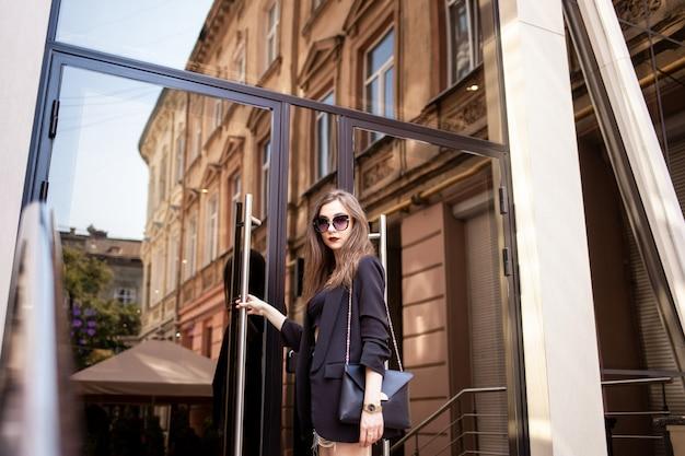 Elegancka młoda biznesowa dziewczyna wchodzi do budynku biurowego