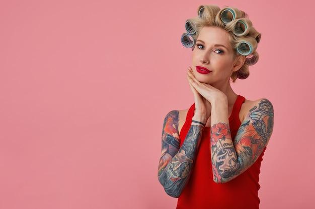 Elegancka młoda blondynka z tatuażami, składającymi ręce pod brodą i patrząc delikatnie w kamerę, robiąc fryzurę i mając świąteczny makijaż, stojąc na różowym tle