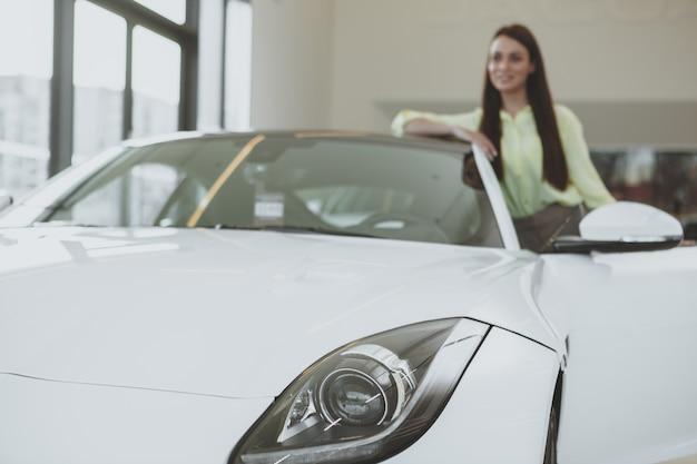 Elegancka młoda kobieta kupuje nowego samochód przy przedstawicielstwem handlowym