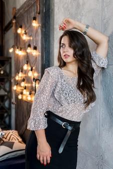 Elegancka młoda kobieta opiera na popielatej ścianie blisko iluminującej żarówki
