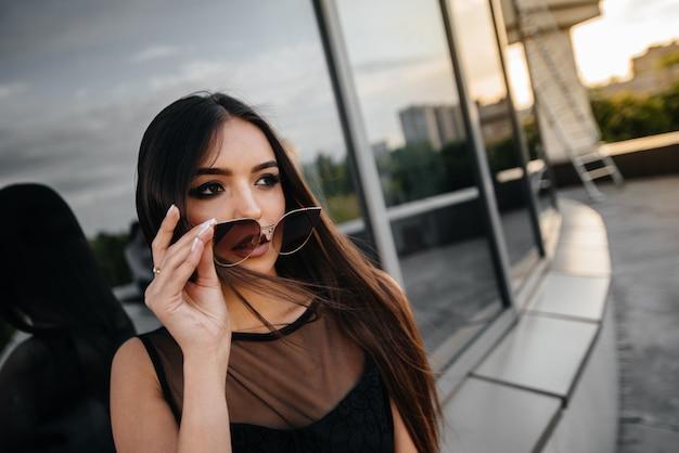 Elegancka młoda kobieta pozuje przed centrum biznesu w czerni. moda i styl