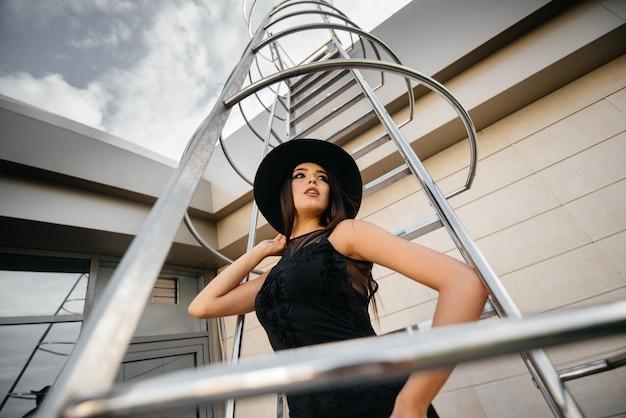 Elegancka młoda kobieta pozuje w kapeluszu na pożarniczej ucieczce centrum biznesu. moda