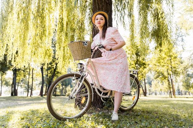 Elegancka młoda kobieta pozuje z rowerem