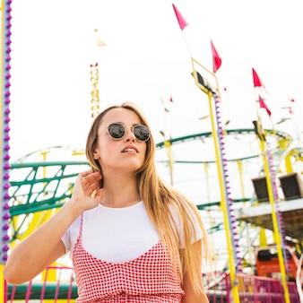 Elegancka młoda kobieta stoi przed roller coaster
