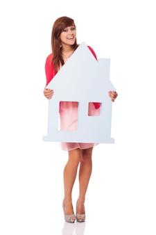 Elegancka młoda kobieta trzyma znak domu