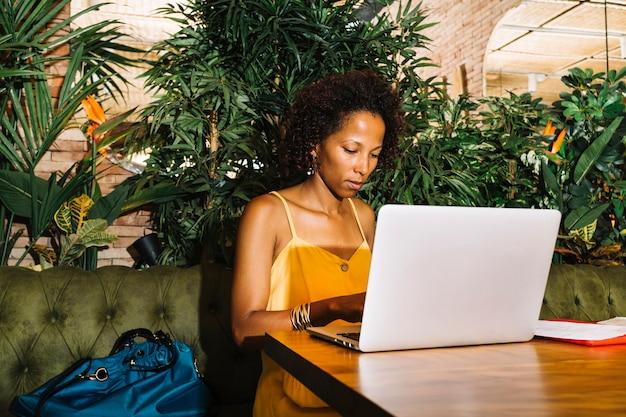 Elegancka młoda kobieta używa laptopu obsiadanie przy restauracja stołem
