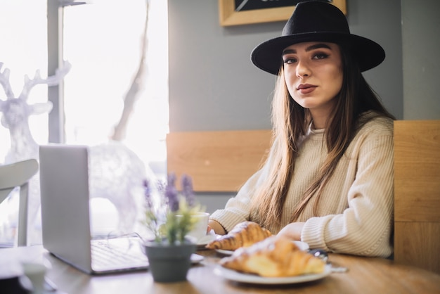 Elegancka młoda kobieta w kapeluszu z laptopem i croissants przy stołem w kawiarni