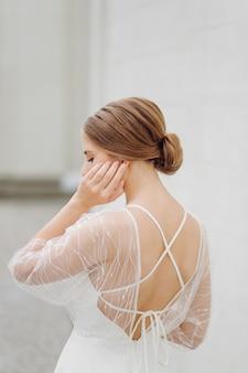 Elegancka młoda kobieta w modnej białej sukni stoi blisko ściany