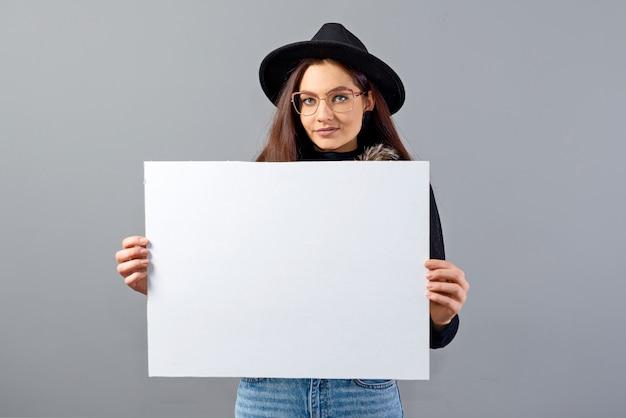 Elegancka młoda kobieta w okularach i kapeluszu pokazuje pusty baner pokładzie, na białym tle na szary, miejsce