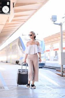Elegancka młoda kobieta z bagażem w koncepcji turystyki dworcowej