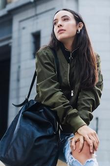 Elegancka młoda kobieta z jej błękitną torebką na naramienny patrzeć daleko od