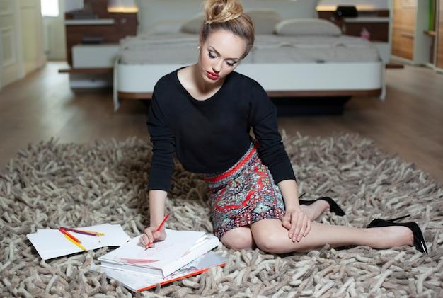 Elegancka młoda kobieta z makijażem i fryzurą, siedząc na podłodze, szkicując na papierze, pracując w domu. obraz pełnej długości.