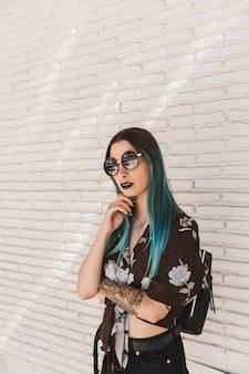 Elegancka młoda kobieta z okularami przeciwsłonecznymi pozuje przed ścianą