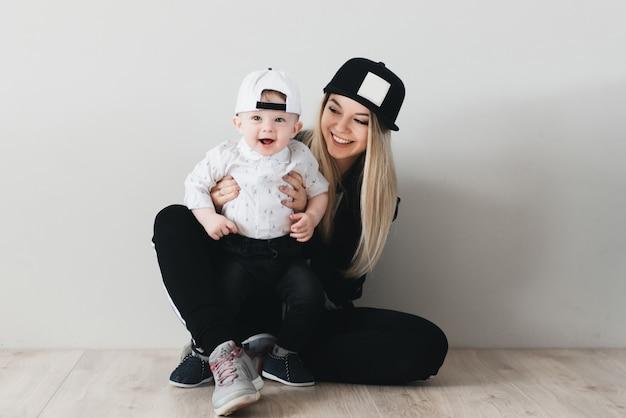 Elegancka młoda mama siedzi i ma zabawę z jej ślicznym roczniakiem dzieckiem odizolowywającym na białym tle w nakrętce. rodzina sportowa