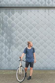 Elegancka młodego człowieka przewożenia plecaka pozycja z jego bicyklem