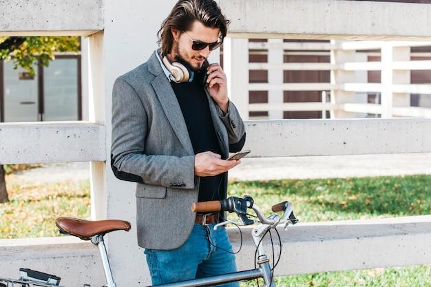 Elegancka młody człowiek pozycja blisko rowerowego używa telefonu komórkowego