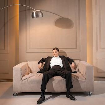 Elegancka modelka pozowanie na kanapie w kolorze kurtki. nowa koncepcja kobiecości
