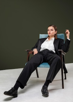 Elegancka modelka siedzi w fotelu w kolorze marynarki. nowa koncepcja kobiecości