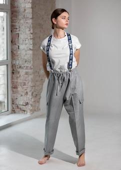 Elegancka modelka tańczy w studio w eleganckiej białej koszuli i szelkach. nowa koncepcja kobiecości