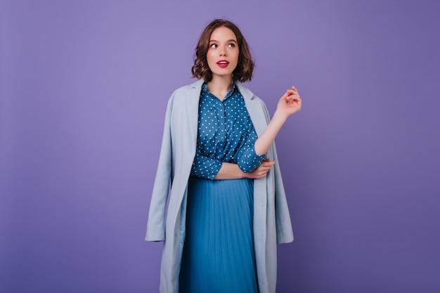 Elegancka modelka w bluzce i długiej spódnicy pozowanie. kryty ujęcie fascynującej kręconej kobiety w niebieskim płaszczu.