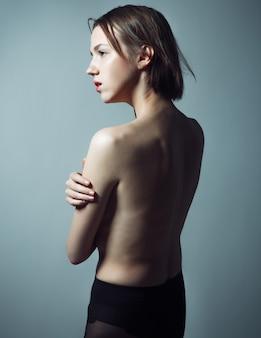 Elegancka naga kobieta z krótkimi blond włosami.