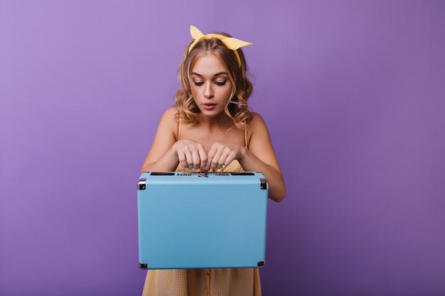 Elegancka opalona dziewczyna patrząc na jej walizkę podróżną. kryty portret uroczej blondynki przygotowuje się do podróży.