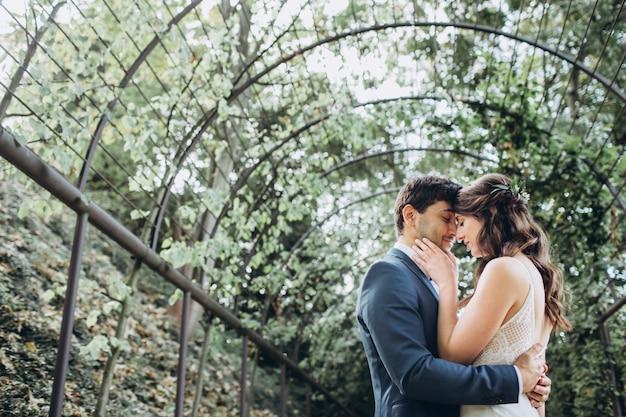 Elegancka panna młoda i pan młody razem pozowanie na zewnątrz w dniu ślubu