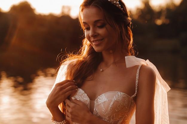 Elegancka panna młoda w białej sukni cieszy się naturą o zachodzie słońca. model w sukni ślubnej na łonie natury w parku. białoruś.