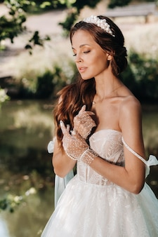 Elegancka panna młoda w białej sukni, rękawiczkach z bukietem na wodospadzie w parku, ciesząc się naturą.modelka w sukni ślubnej i rękawiczkach w lesie.białoruś