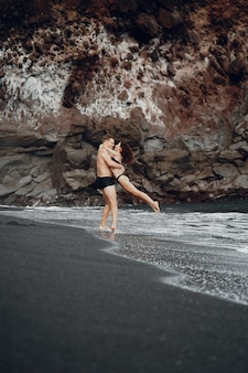 Elegancka para na plaży w pobliżu skał