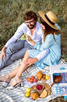 Elegancka para robi smaczny piknik na świeżym powietrzu