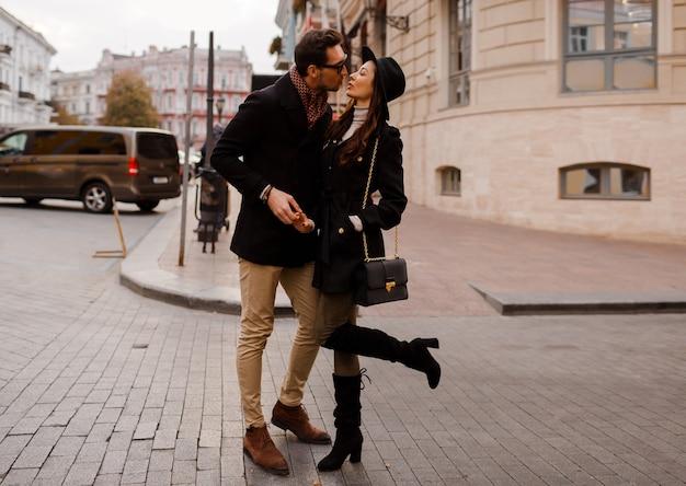 Elegancka para zakochanych spacerując po ulicy podczas wakacji w europie, bawiąc się, całując, przytulając. pełna wysokość.