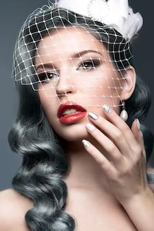 Elegancka piękna dziewczyna ze srebrnymi lokami i welonem. obraz zimowy. piękna twarz. zdjęcie zrobione w studio na szarym tle.