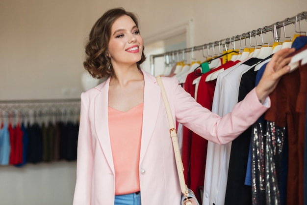 Elegancka piękna kobieta, patrząc na sukienki na wieszakach w butiku mody