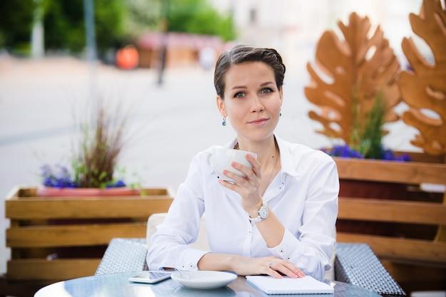 Elegancka piękna kobieta pije kawę przy kawiarnią z notatnikiem