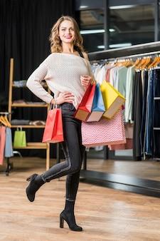 Elegancka piękna kobieta pozuje w butiku z trzymać kolorowego torba na zakupy