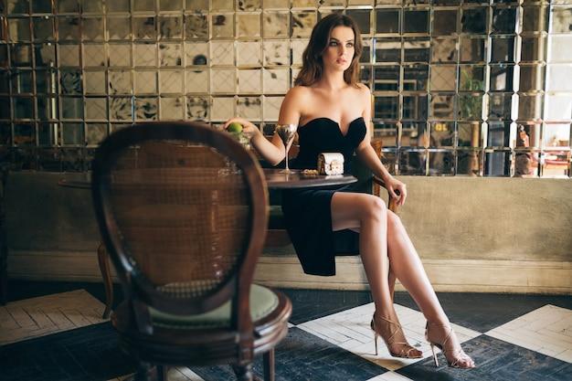 Elegancka piękna kobieta siedząca w kawiarni vintage w czarnej aksamitnej sukience, sukni wieczorowej, bogatej stylowej pani, eleganckim trendzie w modzie, seksownym uwodzicielskim spojrzeniu, atrakcyjnej szczupłej figurze z długimi nogami na obcasach