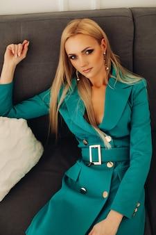 Elegancka piękna kobieta siedzi na kanapie i patrząc z przodu