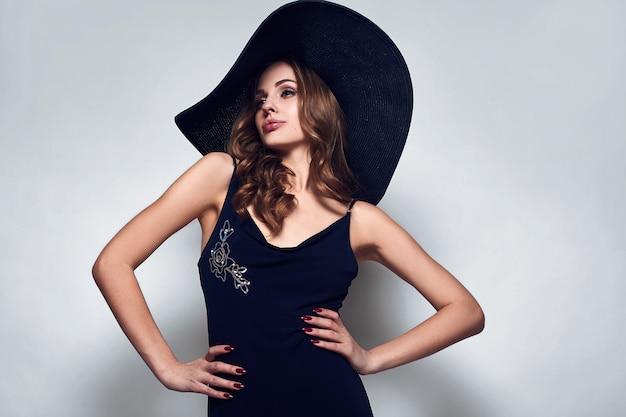 Elegancka piękna kobieta w czarnej sukni i kapeluszu