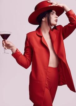 Elegancka piękna kobieta w czerwonym modnym garniturze i kapeluszu z koktajlem