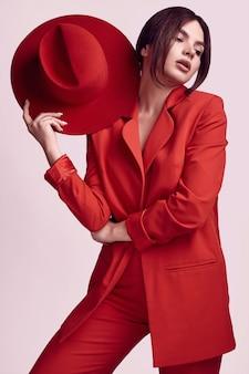 Elegancka piękna kobieta w czerwonym modnym garniturze i szerokim kapeluszu