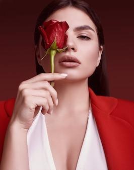 Elegancka piękna kobieta w czerwonym modnym garniturze z różą