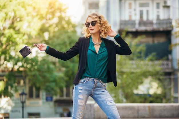 Elegancka piękna kobieta w okularach przeciwsłonecznych, kurtce, dżinsach, zielonej bluzce, wiosenny trend w modzie, trzymająca małą torebkę,
