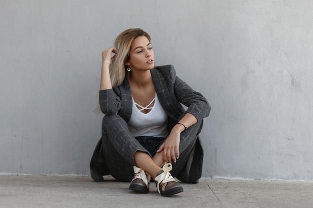 Elegancka piękna młoda kobieta w modnym szarym garniturze z klasyczną kurtką i spodniami odpoczywa w pobliżu szarej ściany na ulicy