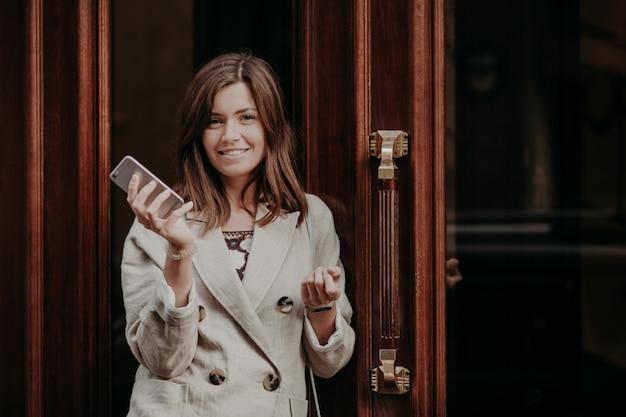 Elegancka, przepiękna dama w płaszczu przeciwdeszczowym, trzyma telefon komórkowy, czeka na telefon