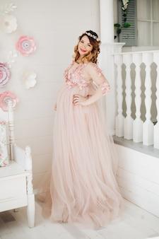 Elegancka przyszła matka pozuje w długiej sukni trzyma jej brzuch