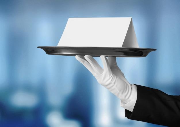 Elegancka ręka kelnera w białej rękawiczce trzymająca płytkę z notatką