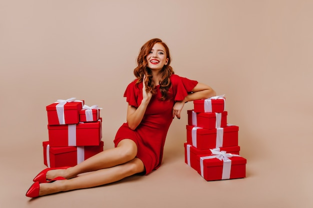 Elegancka ruda kobieta w wysokich obcasach pozowanie na przyjęcie bożonarodzeniowe. kryty zdjęcie uroczej kręconej dziewczyny w czerwonej sukience zabawy w urodziny.