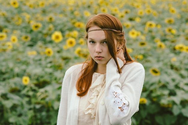 Elegancka rudowłosa kobieta z kolczykiem w polu słoneczników