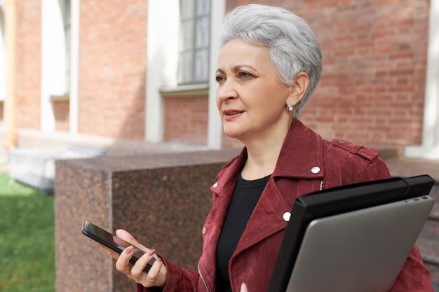 Elegancka siwowłosa kobieta w średnim wieku niosąca laptopa, idąca na spotkanie biznesowe, spieszy się